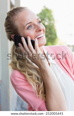 Pretty blonde making a call on a sunny day in the city - stock photo