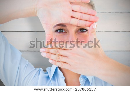 Pretty blonde making a hand gesture against painted blue wooden planks