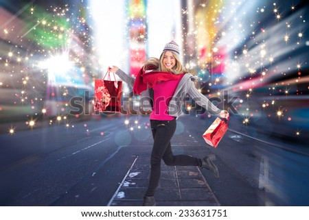 Pretty blonde posing in winter clothes against blurry new york street - stock photo
