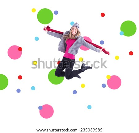 Pretty blonde posing in winter clothes against dot pattern - stock photo