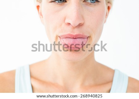 Pretty blonde showing her tongue on white background