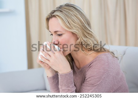 Pretty blonde sitting on couch drinking coffee at home in the living room - stock photo