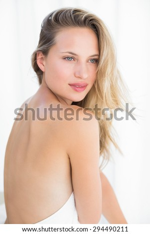 Pretty blonde sitting on massage table at the health spa - stock photo