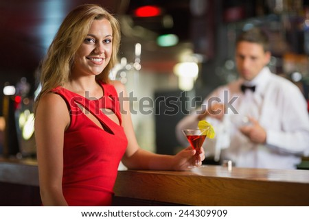 Pretty blonde smiling at camera with cocktail in a bar - stock photo