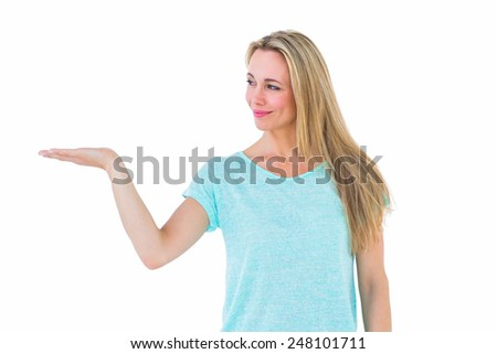 Pretty blonde smiling with hand out on white background - stock photo