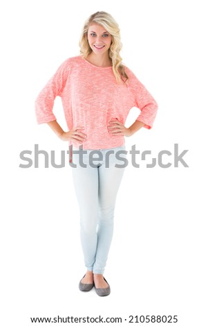 Pretty blonde smiling with hands on hips on white background - stock photo