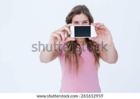 Pretty blonde taking a selfie of herself on white background