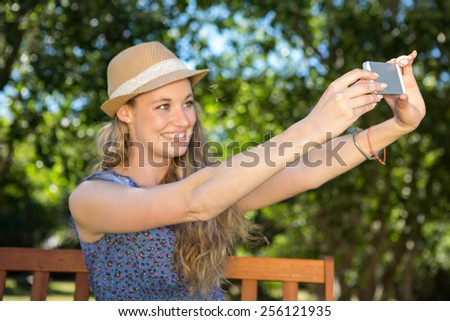 Pretty blonde taking a selfie on a summers day - stock photo