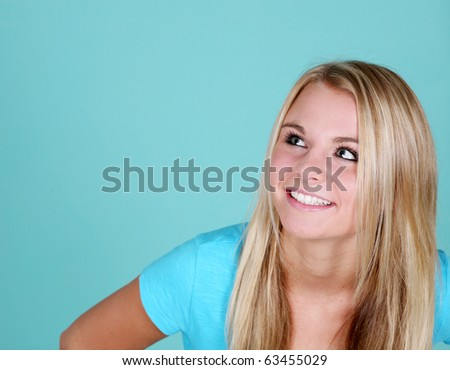pretty blonde teen girl on blue background looking up