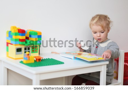 Pretty blonde toddler girl solving puzzles in the book sitting at little white table indoors at home or kindergarten - stock photo