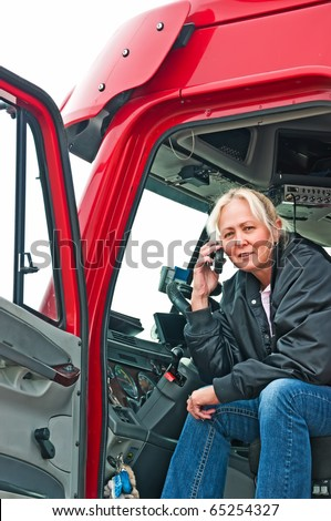 Pretty blonde truck driver getting directions to a delivery site on her cellphone. - stock photo
