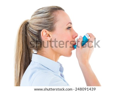 Pretty blonde using an asthma inhaler on white bakcground - stock photo