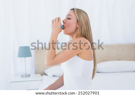 Pretty blonde using asthma inhaler at home in the bedroom - stock photo