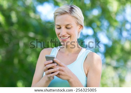Pretty blonde using smartphone on a sunny day - stock photo
