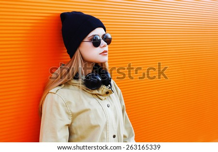 Pretty blonde wearing a black hat and headphones listens to music enjoys freedom, cool hipster girl in the city against a colorful wall, street fashion concept, urban style - stock photo