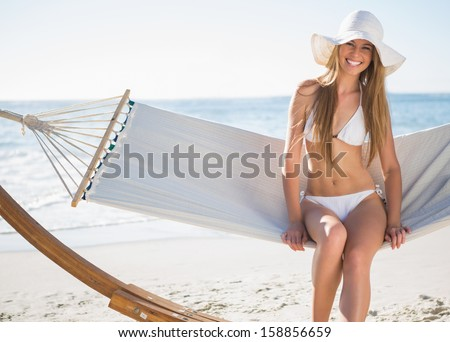 Pretty blonde wearing bikini and sunhat sitting on hammock and smiling on the beach - stock photo