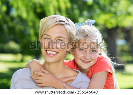 Pretty blonde with her daughter in the park on a sunny day