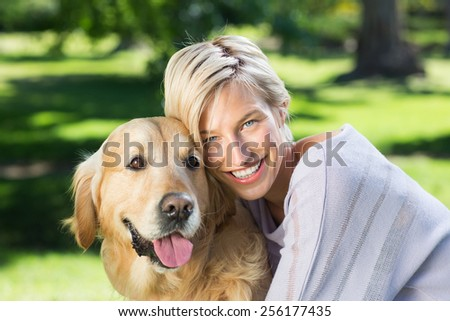 Pretty blonde with her dog in the park on a sunny day - stock photo
