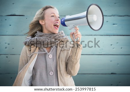 Pretty blonde with megaphone against painted blue wooden planks - stock photo