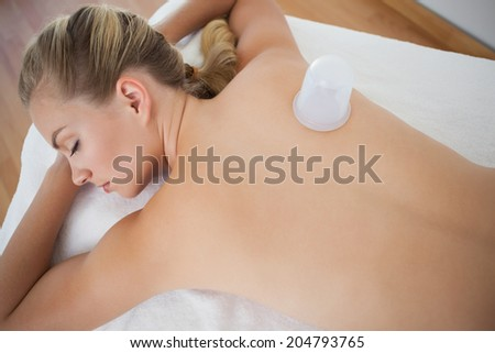 Pretty blonde with vacuum cup on her back at the health spa