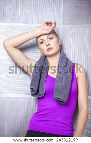 Pretty blonde woman after fitness training standing tired against the wall  - stock photo