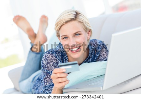 Pretty blonde woman doing online shopping in the living room - stock photo