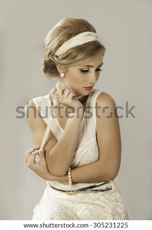 Pretty blonde woman dressed in a vintage fifties lace dress with retro hairstyle and pearl jewelry - stock photo