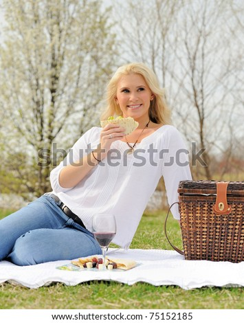 Pretty blonde woman eating sandwich on a picnic - pita with basket in photo