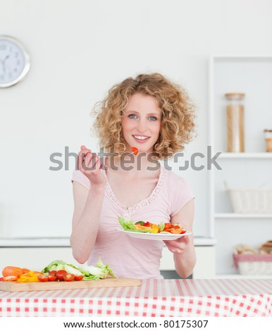 Pretty blonde woman eating some vegetables in the kitchen in her apartment - stock photo