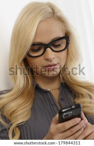 Pretty blonde woman in black framed glasses, using mobilephone. - stock photo
