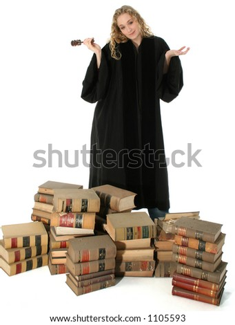 Pretty blonde woman judge in black robe with gavel standing behind stack of 70 year old law books. - stock photo