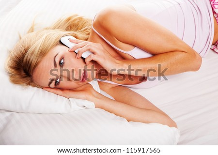 Pretty blonde woman lying in her bed listening to a conversation on her mobile with wide open eyes - stock photo