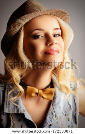 Pretty blonde woman posing at studio. Jeans style.
