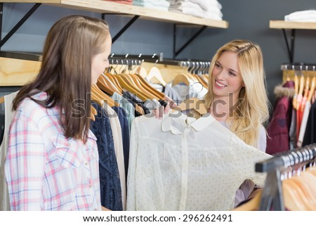 Pretty blonde woman showing clothes to her friend in clothes store