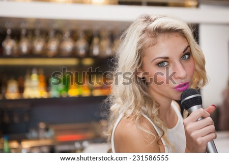 Pretty blonde woman singing while looking at camera at the nightclub - stock photo
