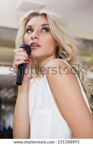 Pretty blonde woman singing while looking up at the nightclub - stock photo