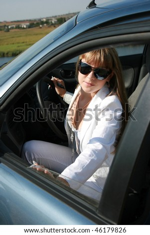 Pretty blonde woman sitting in the car
