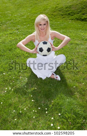 Pretty blonde woman sitting on lush green grass holding a football in front of her chest - stock photo