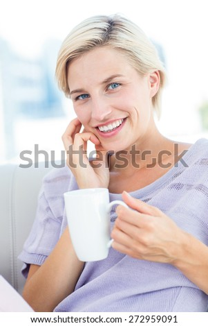 Pretty blonde woman sitting on the couch and holding a mug in the living room