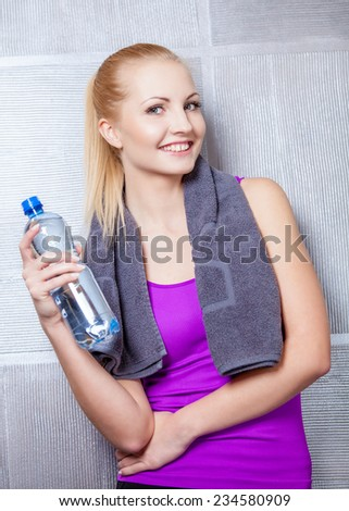 Pretty blonde woman smiling after fitness training drinking water - stock photo