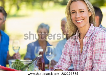 Pretty blonde woman smiling at camera during a picnic on a sunny day - stock photo