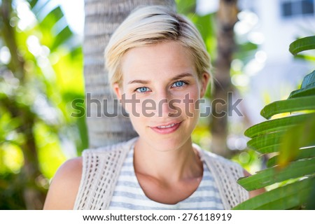 Pretty blonde woman smiling at the camera in the park - stock photo