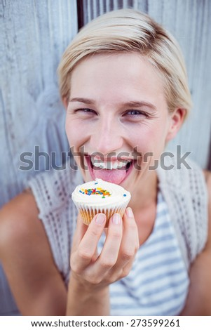 Pretty blonde woman tasting the cupcake on wooden background - stock photo