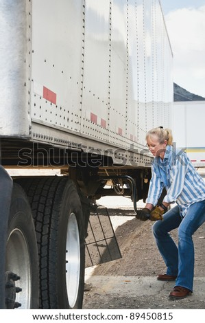 Pretty blonde woman truck driver cranking the dolly handle to raise the legs of a trailer after backing her tractor under it. - stock photo