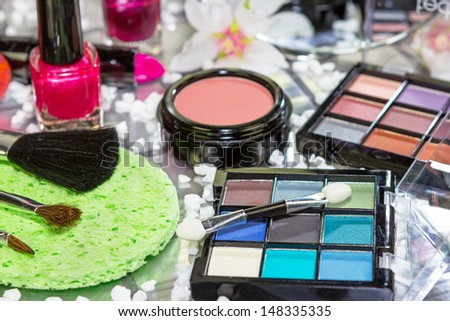 Pretty blue eye shadow in a compact arranged with brushes, blusher, lipstick and nail lacquer ready for a young woman to beautify herself - stock photo