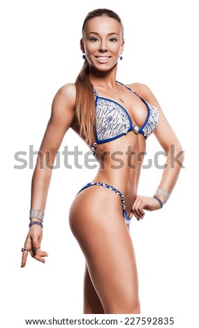 pretty bodybuilder woman smiling in blue bikini on white background - stock photo