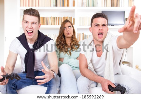 pretty bored women between two casual passionate men playing video game with joystick at living room atmosphere - stock photo