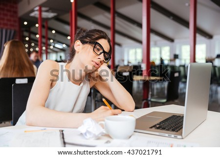 Pretty bored young businesswoman working using laptop in office - stock photo