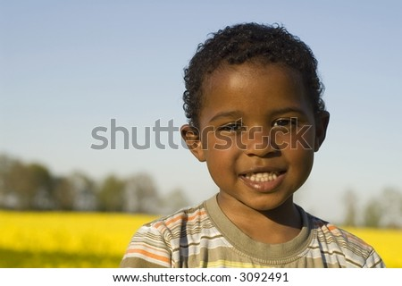 Pretty boy in a yellow field - stock photo