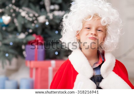 Pretty boy is making fun near Christmas tree. He is wearing red clothing of Santa Claus and white wig.  The boy is looking forward happily and smiling - stock photo
